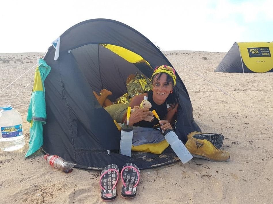 La Bee est allongée dans sa tente du Half Marathon des Sable, la tête à l'extérieur,et le visage souriant. Elle tient une gourde dans sa main gauche et sa mascotte ( le cham'Waa) dans sa la gauche.