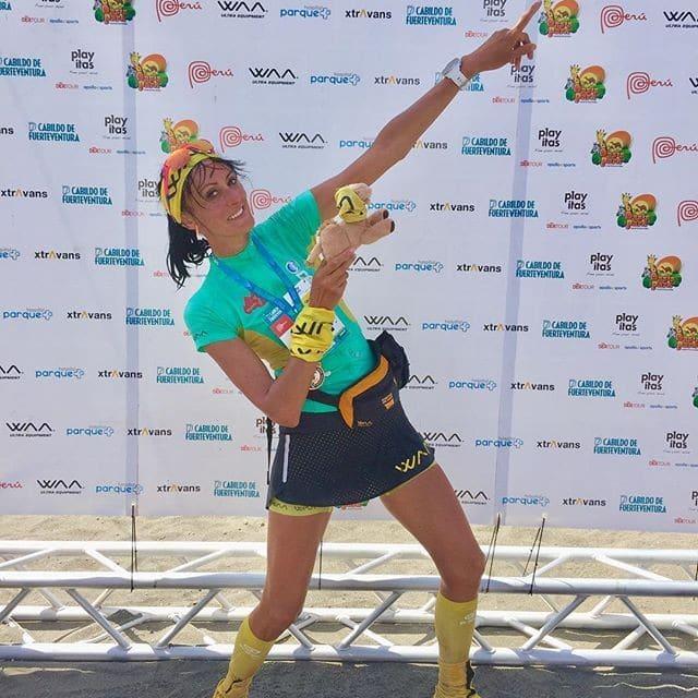 Photo de la Bee à l'arrivée du Half Marathon des Sables. Son bras gauche est tendu et levé et son index pointe vers le ciel.