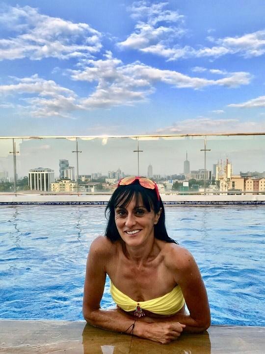 La Bee est au bord d'une piscine sur un toit. Derrière, on a la vue sur la ville de Nairobi : immeubles, parcs...