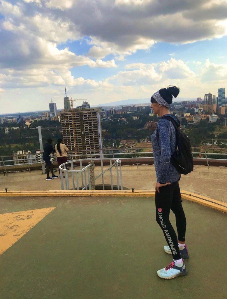 La Bee est en haut de trente étages, pensive. La vue domine Nairobie, capitale du Kenya. On voit un mélange de gratte-ciel, de nature et de constructions diverses.