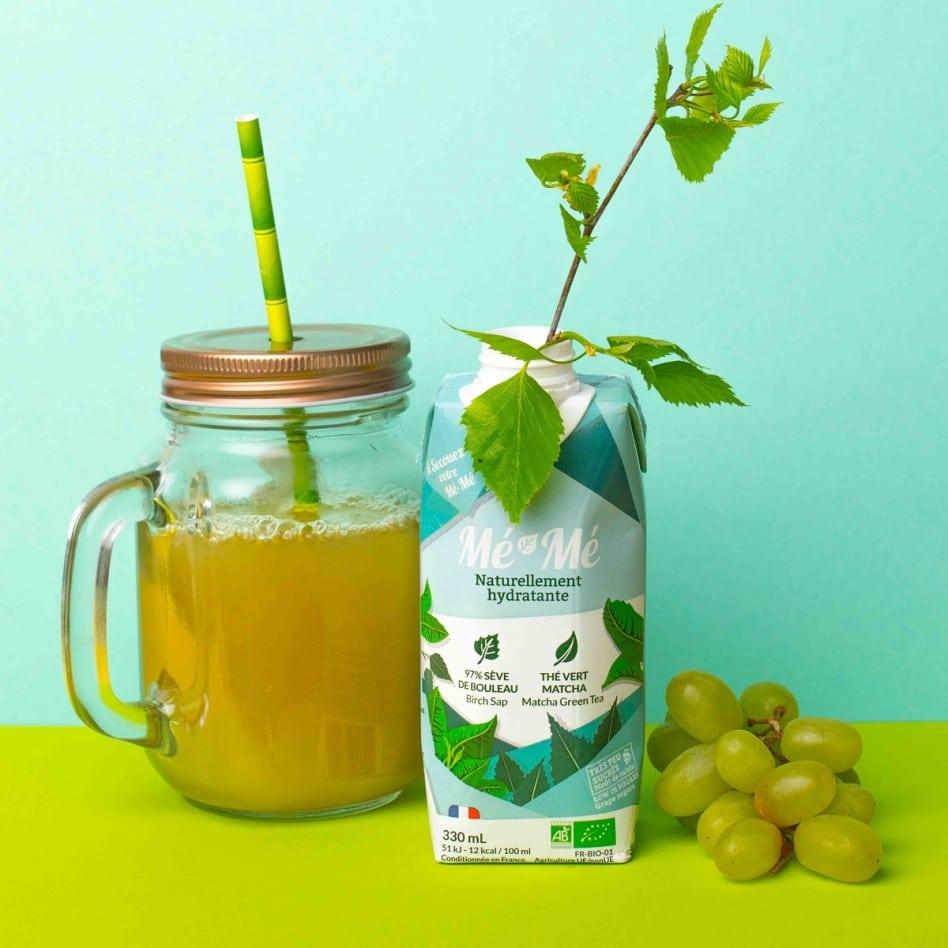 On voit un verre de boisson naturelle bio Mé-Mé hydratante avec une paille. La brique d'emballage est à côté. Une tige de menthe en sort.