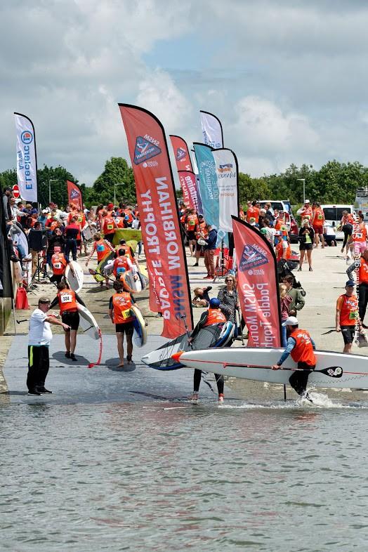 Les concurrents doivent franchir la ligne d'arrivée de la course de stand up paddle avec leur paddle sous le bras