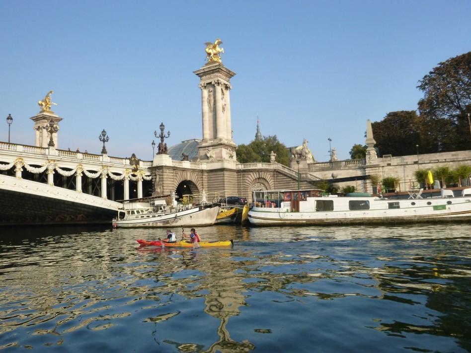 Des concurrents passent en kayak sous un pont de Paris