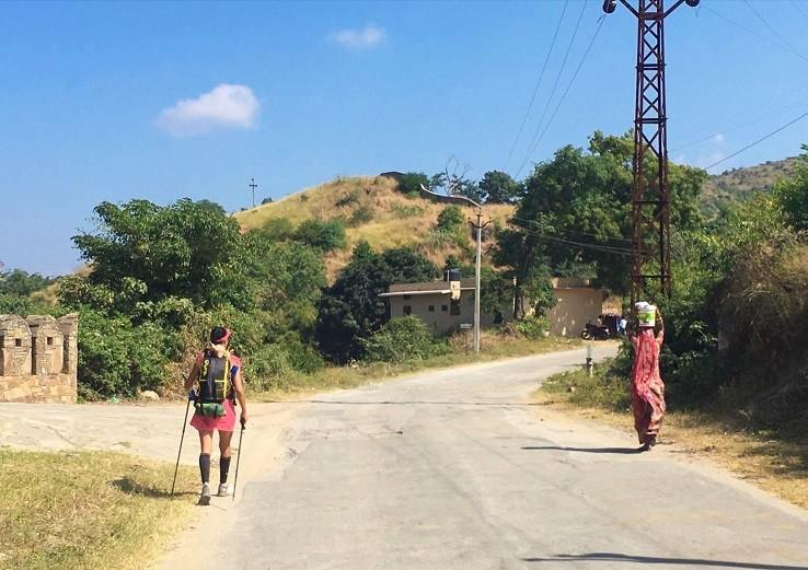 La Bee marche sur le côté de la route ; de l'autre côté, une femme indienne porte un seau.