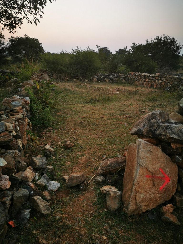 Le muret derrière lequel nous nous sommes cachées. La flèche rose sur le rocher est le balisage sommaire.