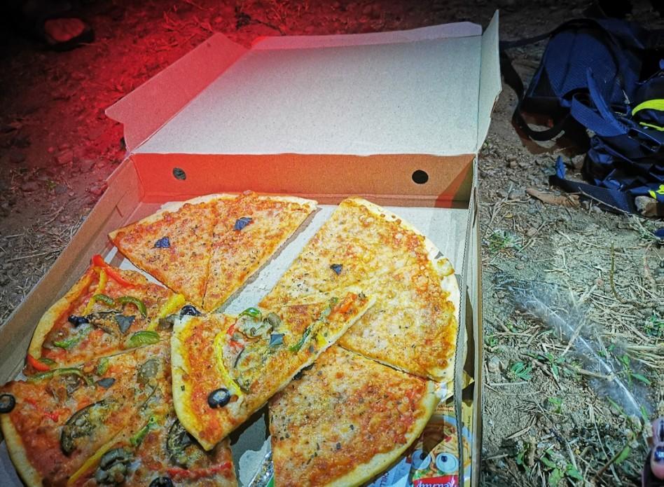 Une boîte avec une pizza est posée devant la tente.