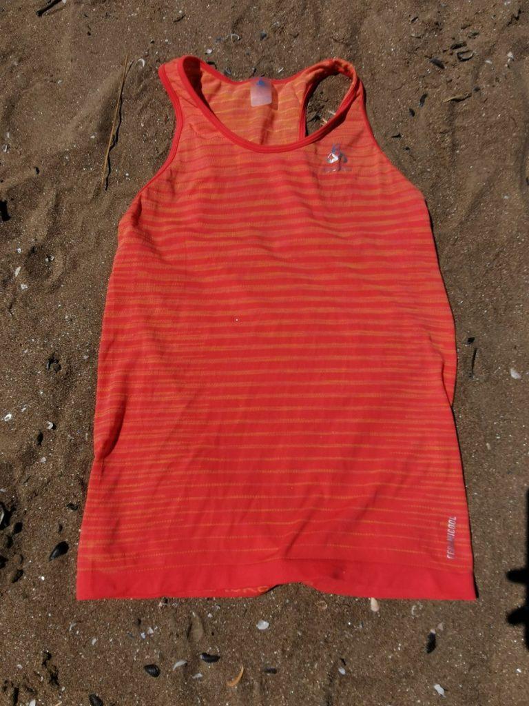 Photo du débardeur ODLO sur le sable de la plage. Couleur orange